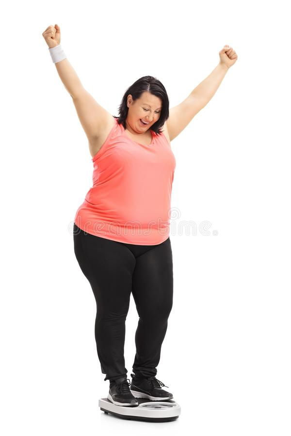 Donna di peso eccessivo su una bilancia che gesturing felicità immagini stock