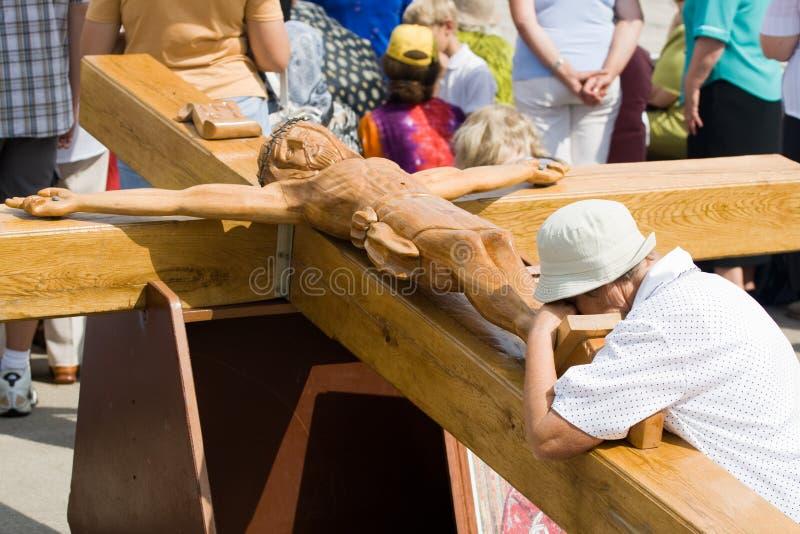 Donna di preghiera alla grande croce di legno fotografia stock