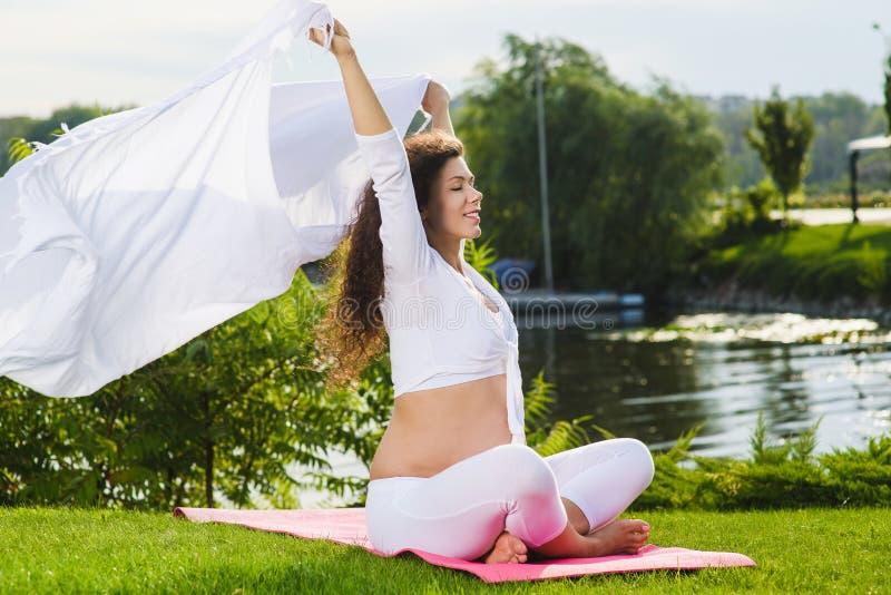 Donna di Pregnat che tiene tessuto bianco su vento fotografia stock