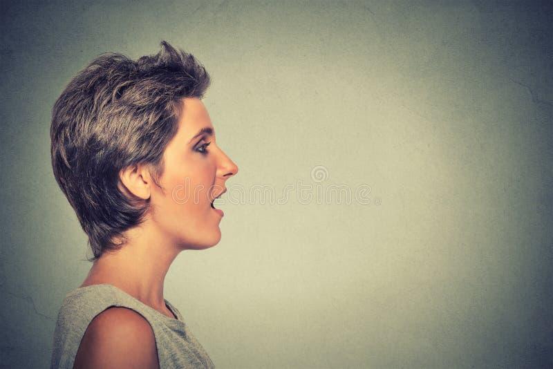 Donna di profilo di vista laterale che parla con il suono che esce dalla sua bocca aperta fotografie stock