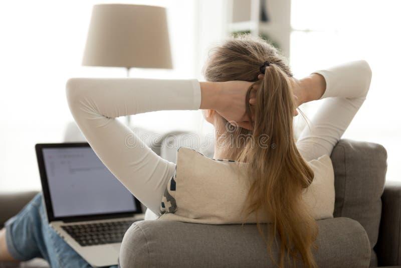 Donna di retrovisione che si rilassa con il computer portatile sul sofà comodo a casa immagini stock