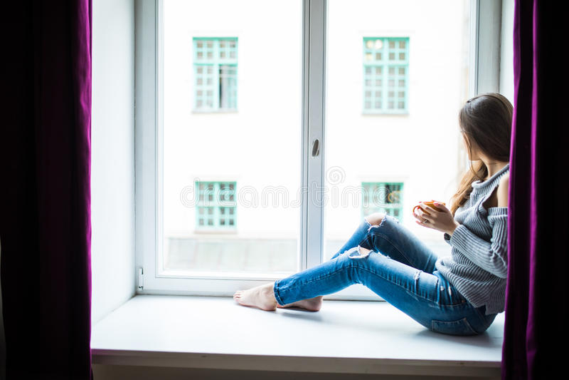 Donna di riposo e di pensiero Ragazza calma con la tazza di tè o di caffè che si siede e che beve sul finestra-davanzale a casa fotografie stock libere da diritti