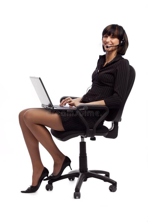 Donna di risata del brunette nella seduta scura del vestito fotografie stock libere da diritti
