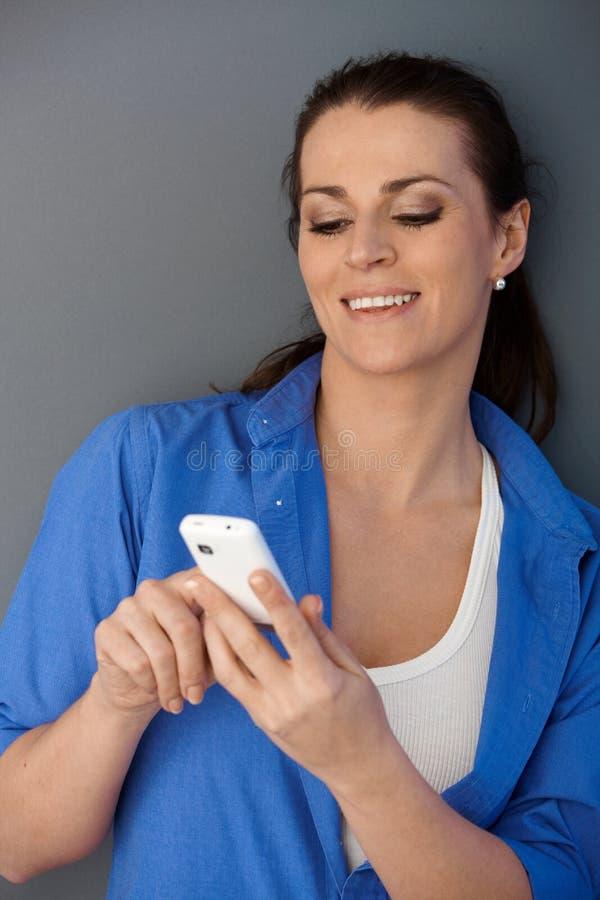 Donna di risata dell'metà di-adulto che texting fotografia stock