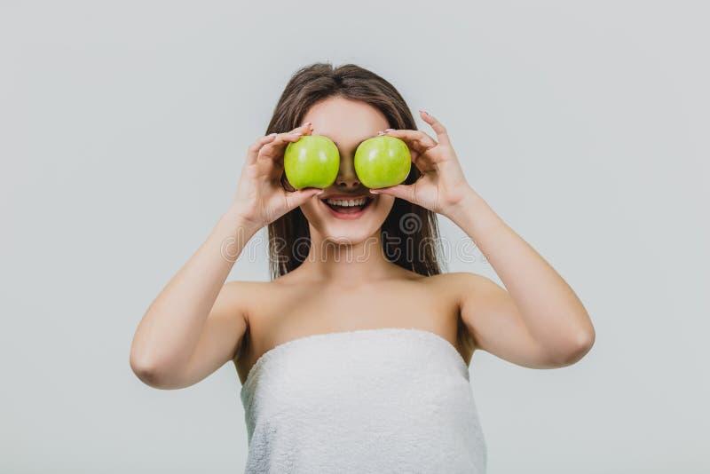 Donna di risata divertente che tiene due mele verdi nei suoi occhi Fondo bianco di un concetto sano di cibo Dieta immagine stock