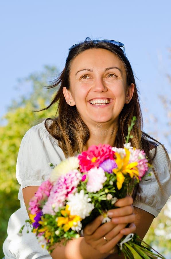 Donna di risata felice con i fiori fotografia stock