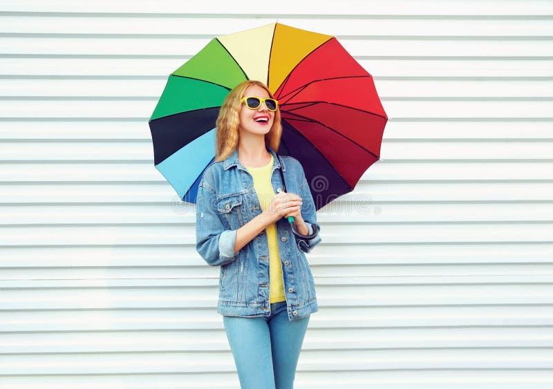 Donna di risata felice con l'ombrello variopinto nel giorno di autunno sulla parete bianca immagini stock