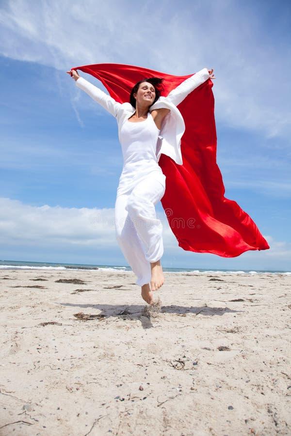 Donna di salto della sciarpa del litorale fotografia stock