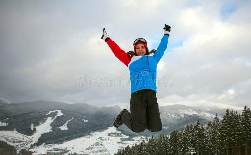 Donna di salto felice nell'inverno nella stazione sciistica immagine stock libera da diritti