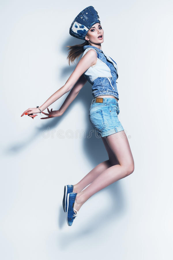 Donna di salto in shorts blu e cappello del denim fotografia stock libera da diritti