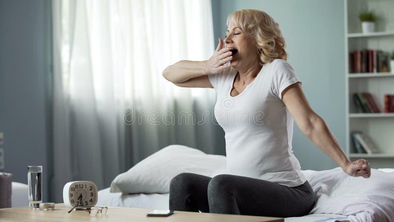 Donna di sbadiglio felice che si siede sul letto, mattina di fine settimana, salute un'armonia immagini stock