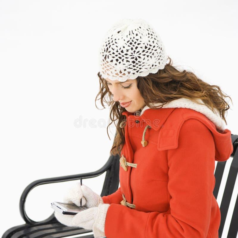 Donna di seduta con PDA. fotografia stock libera da diritti