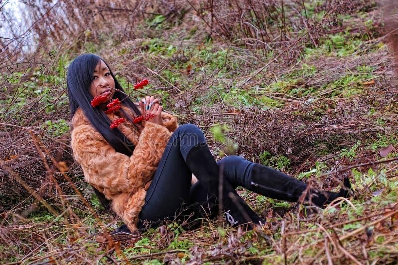 Donna di seduta nel campo immagine stock