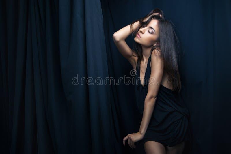 Donna di Sensuall in biancheria intima, fondo scuro fotografia stock