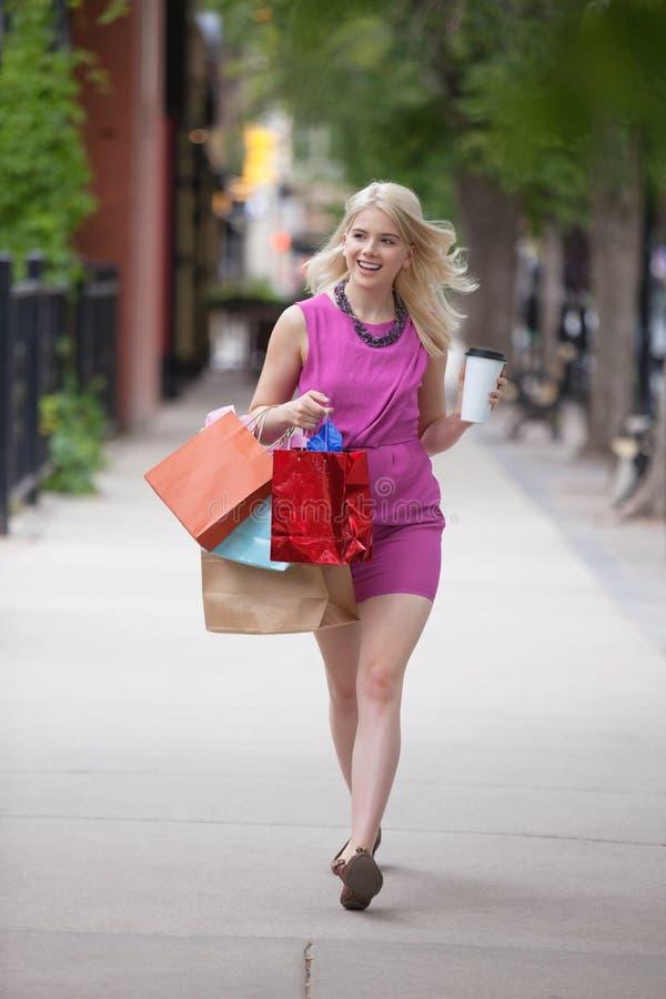 Donna di Shopaholic con la tazza di caffè eliminabile fotografia stock libera da diritti