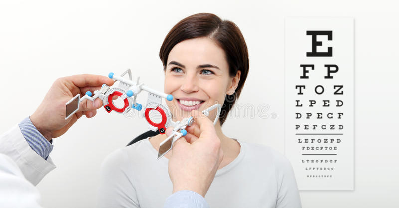 Donna di sorriso che fa misura di vista con la struttura e il visu di prova fotografie stock libere da diritti