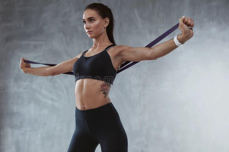 Donna di sport in abiti sportivi di modo che si esercita con la banda elastica immagini stock libere da diritti