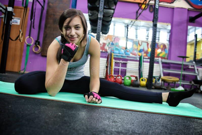 Donna di sport che fa allungando esercizio di forma fisica immagini stock