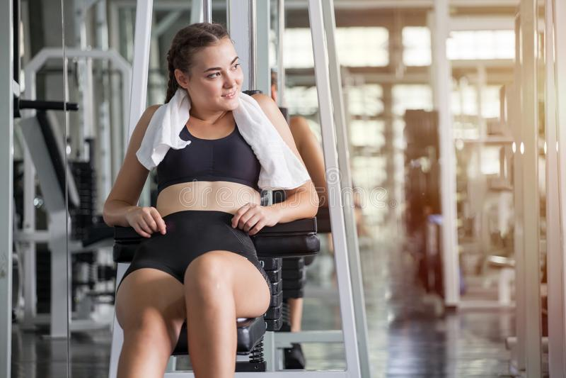 donna di sport che prende una rottura dopo gli esercizi con l'asciugamano sul banco in palestra Allenamento di seduta di resto de fotografia stock libera da diritti