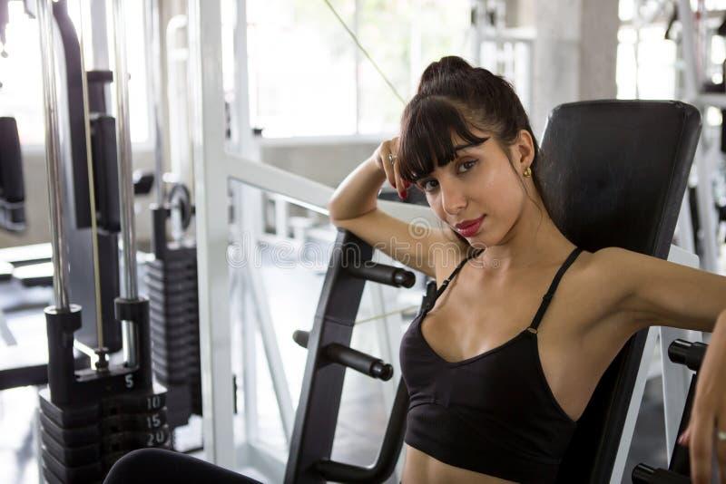 donna di sport che prende una rottura dopo gli esercizi sul banco in palestra Allenamento di seduta di resto della giovane ragazz fotografia stock libera da diritti