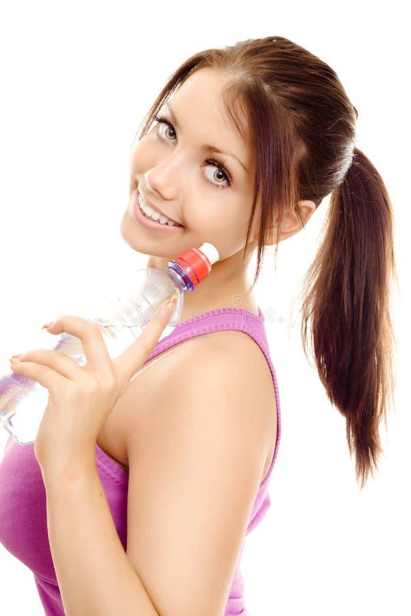 Donna di sport con il sorriso dell'acqua di bottiglia immagini stock