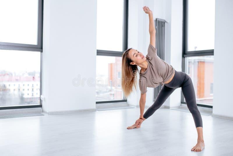 Donna di Sweaaty concentrata su ginnastica nello studio di forma fisica fotografie stock libere da diritti