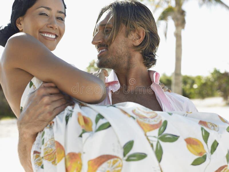 Donna di trasporto dell'uomo felice sulla spiaggia fotografia stock