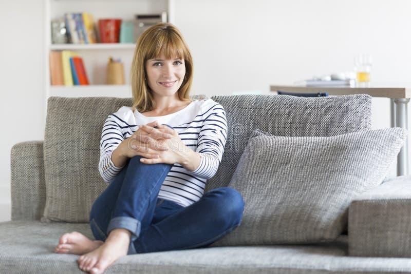 Donna di trenta anni naturale messa sullo strato nella casa moderna fotografia stock libera da diritti