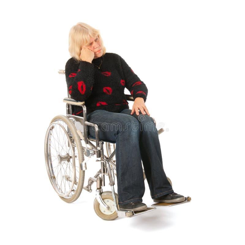 Donna di tristezza dell'età matura nella sedia a rotelle immagini stock