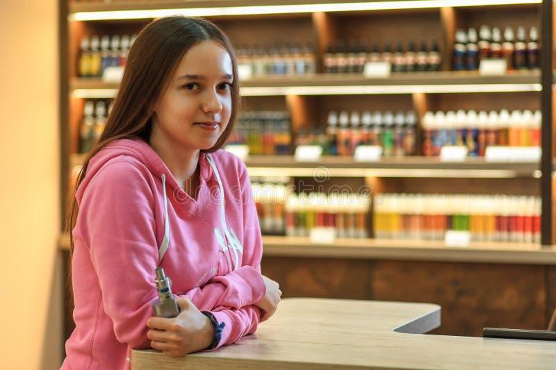 Donna di Vape Giovane ragazza sveglia in maglia con cappuccio rosa che fuma una sigaretta elettronica immagini stock