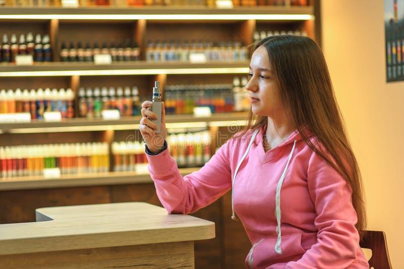 Donna di Vape Giovane ragazza sveglia in maglia con cappuccio rosa che fuma una sigaretta elettronica fotografia stock libera da diritti