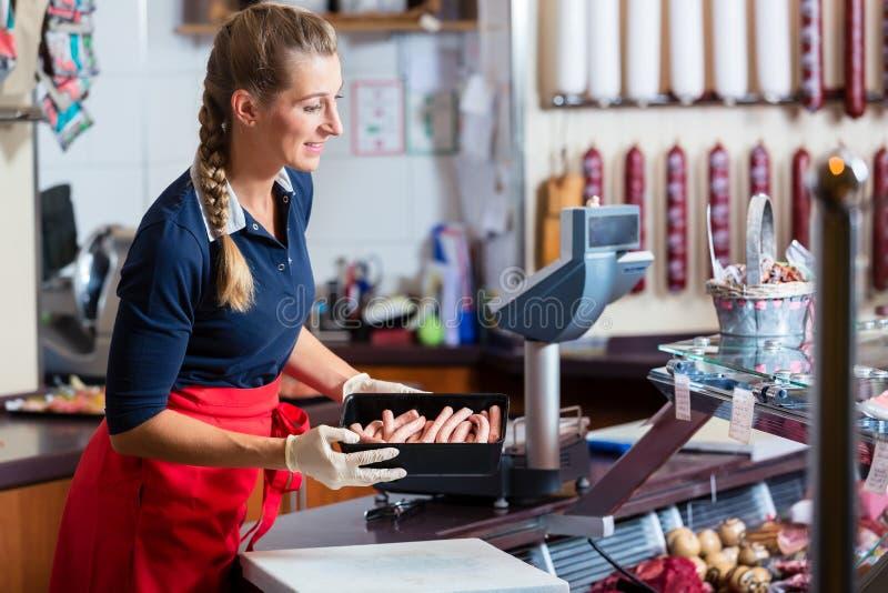 Donna di vendite in di macelleria che mette i generi differenti di carne nell'esposizione immagini stock libere da diritti