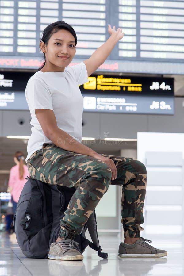 Donna di viaggio con uno zaino che mostra un segno immagini stock libere da diritti