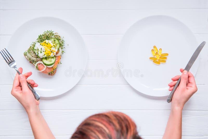 Donna di vista superiore con la coltelleria in mani che scelgono fra l'alimento sano o le pillole mediche sui piatti bianchi e su fotografia stock
