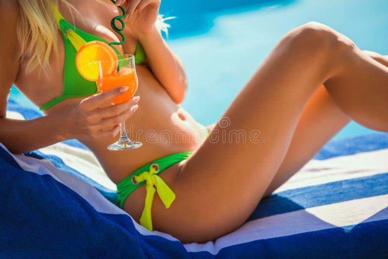 Donna di Woung con il vetro di cocktail vicino alla piscina su uno sdraio fotografie stock