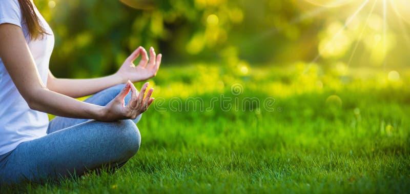 Donna di yoga che medita al tramonto immagini stock