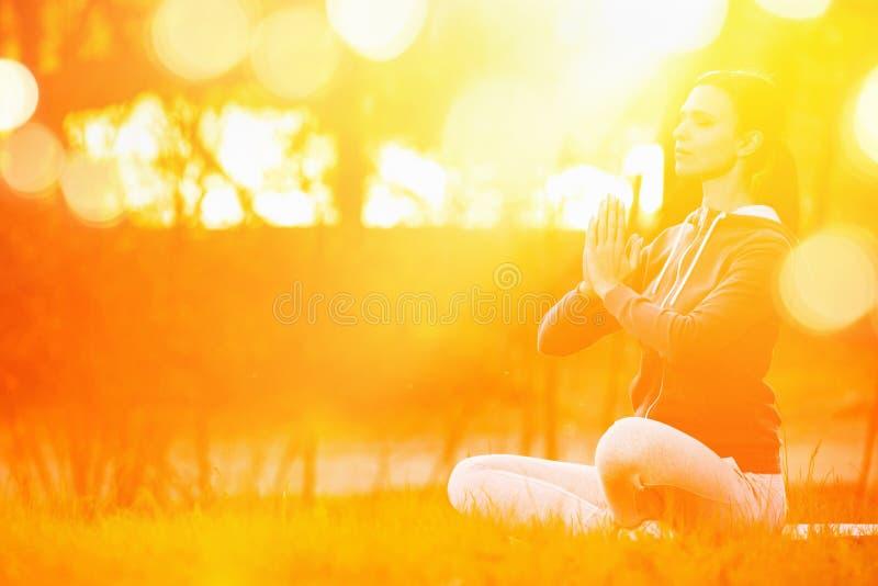 Donna di yoga che medita al tramonto fotografia stock