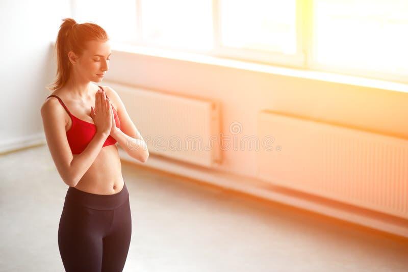 Donna di yoga che medita e che fa un simbolo di zen con le sue mani immagine stock libera da diritti