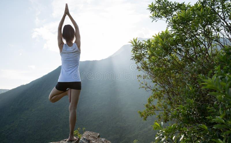 Donna di yoga che medita su bordo della scogliera del picco di montagna fotografie stock