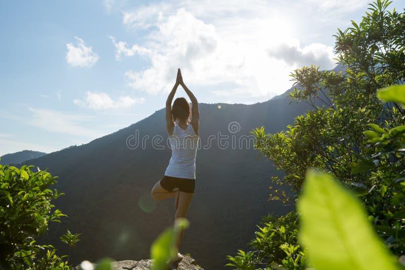Donna di yoga che medita su bordo della scogliera del picco di montagna immagine stock libera da diritti