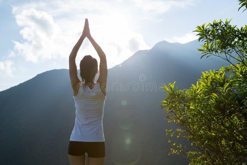 Donna di yoga che medita su bordo della scogliera del picco di montagna fotografie stock libere da diritti