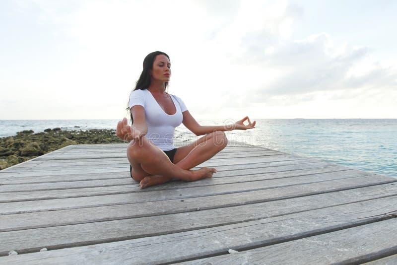 Donna di yoga che meditating vicino al mare immagini stock libere da diritti