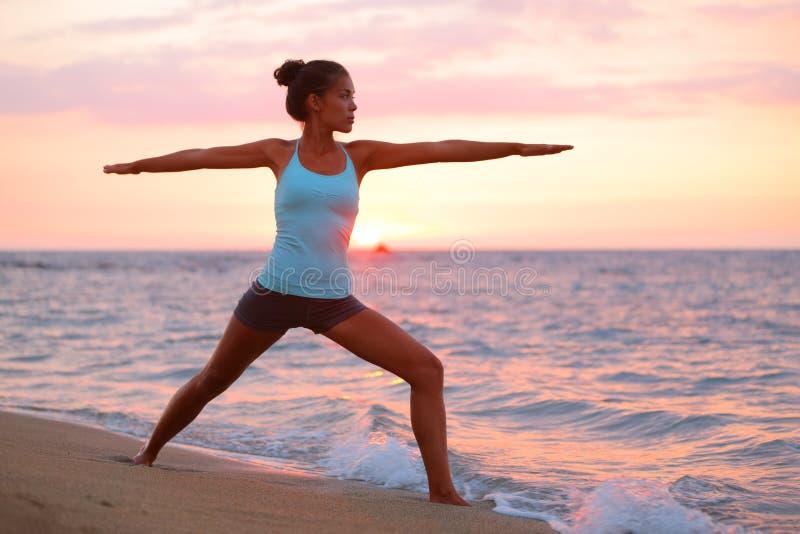 Donna di yoga nel meditare nella posa del guerriero alla spiaggia fotografia stock libera da diritti