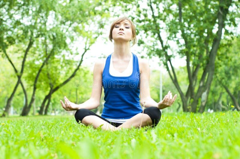 Donna di yoga su erba verde immagine stock