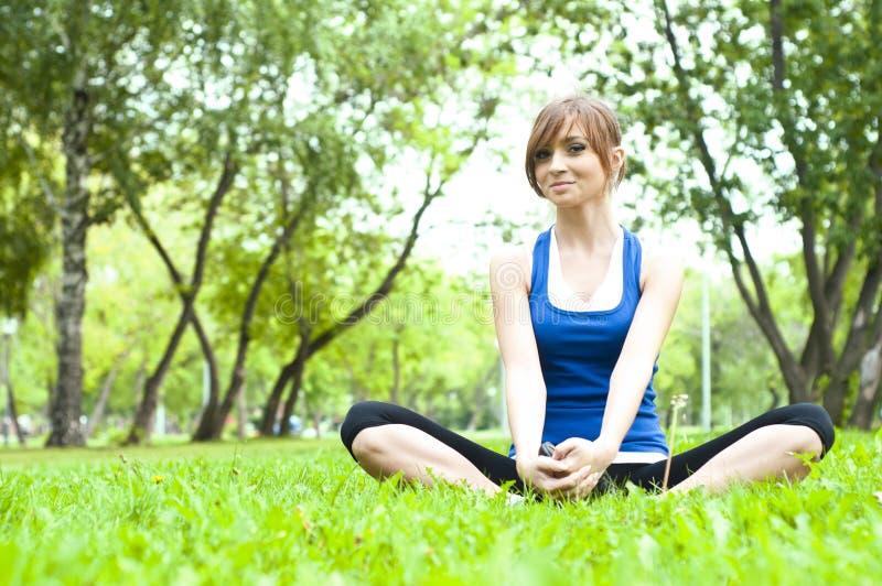 Donna di yoga su erba verde fotografie stock libere da diritti