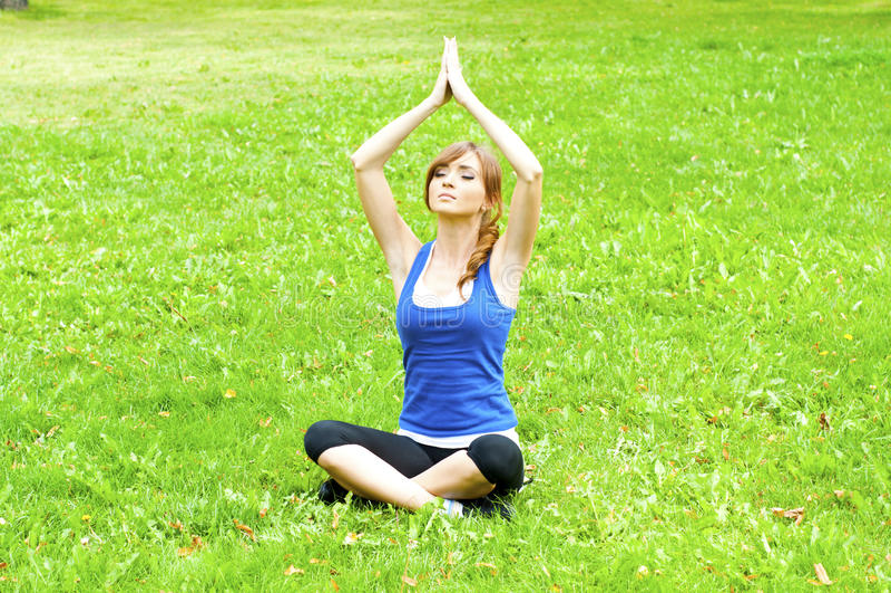 Donna di yoga su erba verde immagini stock