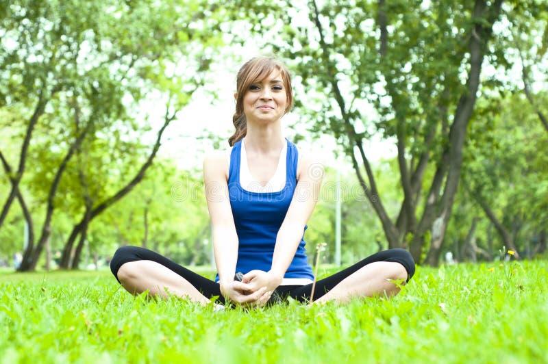 Donna di yoga su erba verde immagini stock libere da diritti
