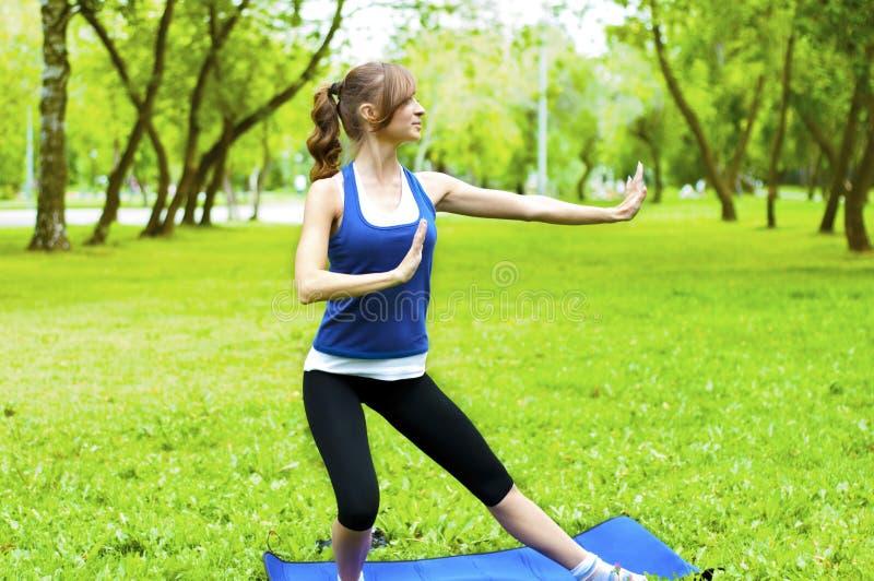 Donna di yoga su erba verde fotografia stock