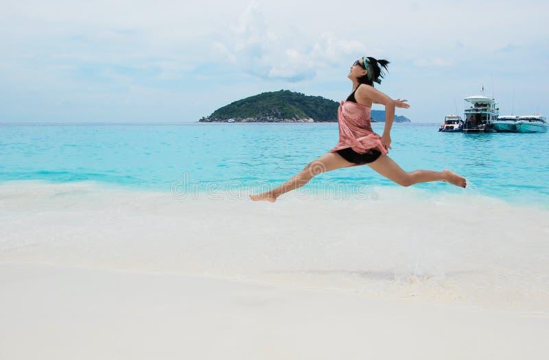 Donna di Yong che salta su una spiaggia immagini stock