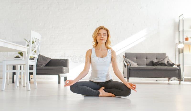 Donna di Yuong che si siede sul pavimento nella posa di yoga fotografie stock libere da diritti